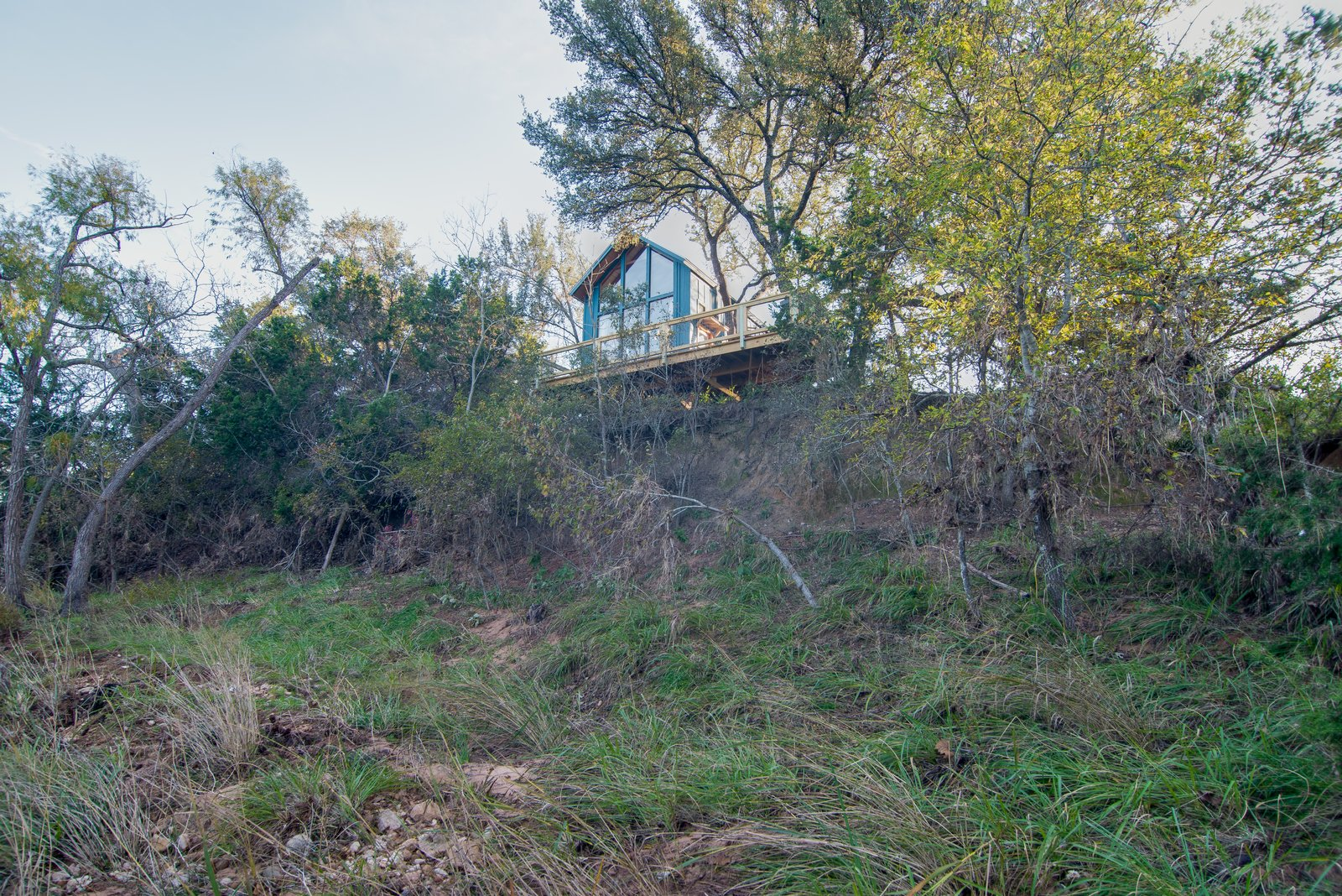 Exterior, Metal Roof Material, Treehouse Building Type, Gable RoofLine, and Wood Siding Material The Sycamore tree house is perched on hill above a creek.  Photo 5 of 10 in Book a Stay in This Whimsical Trio of Tiny Tree Houses
