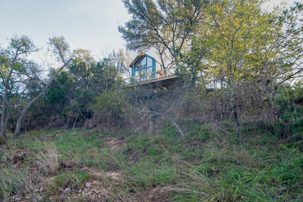 The Sycamore tree house is perched on hill above a creek.