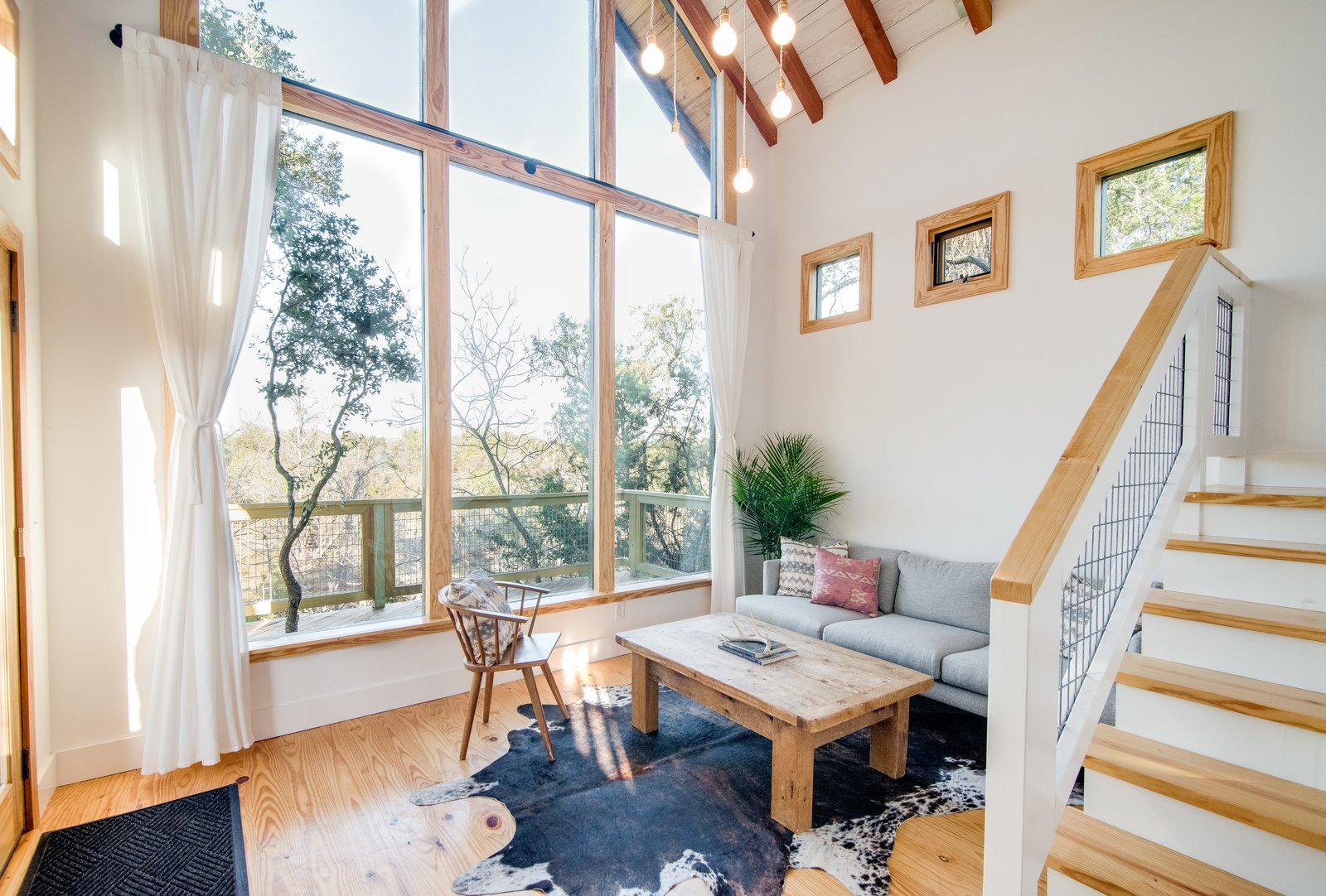 Living Room, Coffee Tables, Light Hardwood Floor, Sofa, Ceiling Lighting, and Chair A window wall connects the living area of The Sycamore to the outdoors.  Photo 6 of 10 in Book a Stay in This Whimsical Trio of Tiny Tree Houses