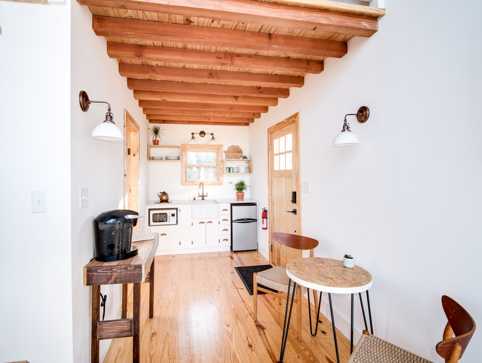 Kitchen, Wall Lighting, White Cabinet, Quartzite Counter, Microwave, Light Hardwood Floor, Refrigerator, Cooktops, and Drop In Sink The kitchen in The Sycamore features white-painted cabinetry, pine ceiling beams and flooring.  Photo 7 of 10 in Book a Stay in This Whimsical Trio of Tiny Tree Houses
