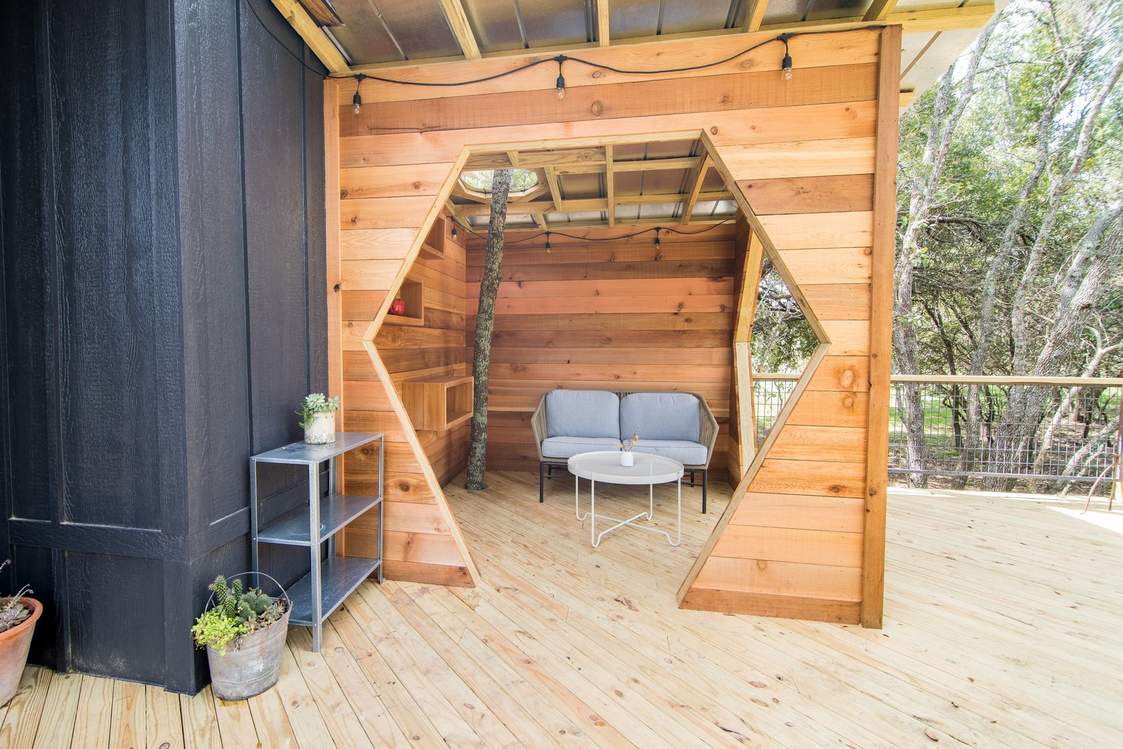 Exterior, Metal Roof Material, Treehouse Building Type, and Wood Siding Material The Sapling showcases a tree growing through a gazebo with a hexagonal opening on the rear deck.  Photo 9 of 10 in Book a Stay in This Whimsical Trio of Tiny Tree Houses