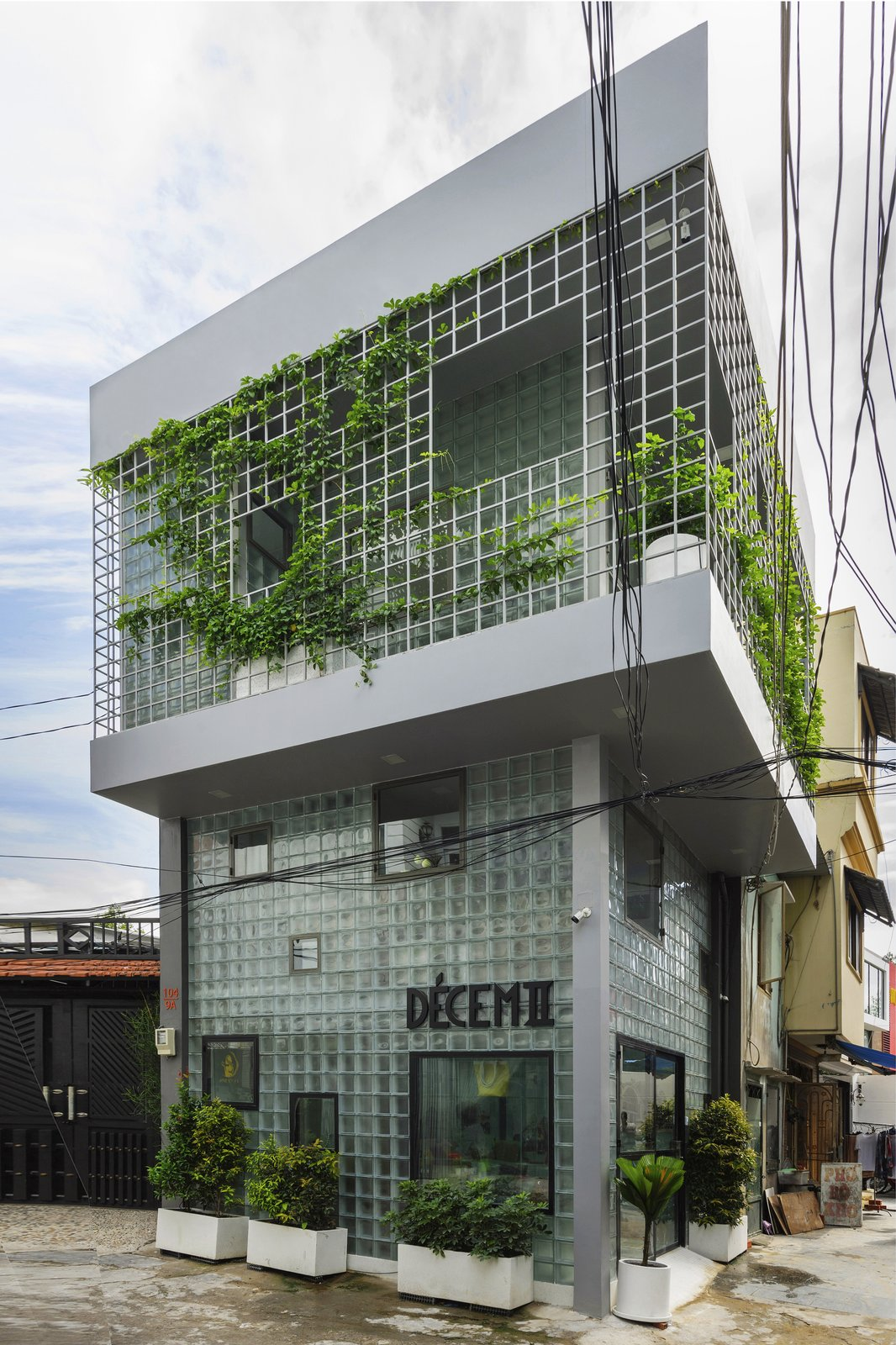 """Exterior, Flat RoofLine, and House Building Type The micro house and boutique in <span style=""""font-family: Theinhardt, -apple-system, BlinkMacSystemFont, &quot;Segoe UI&quot;, Roboto, Oxygen-Sans, Ubuntu, Cantarell, &quot;Helvetica Neue&quot;, sans-serif;"""">Ho Chi Minh City, Vietnam,</span><span style=""""font-family: Theinhardt, -apple-system, BlinkMacSystemFont, &quot;Segoe UI&quot;, Roboto, Oxygen-Sans, Ubuntu, Cantarell, &quot;Helvetica Neue&quot;, sans-serif;""""> designed by ROOM+ Design &amp; Build features glass-block siding.</span>  Photo 2 of 12 in This Vietnamese Micro Home Is as Practical as It Is Radiant"""