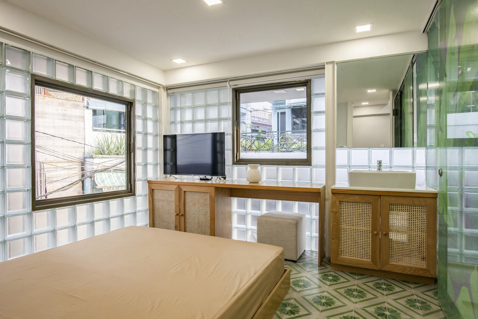 Bedroom, Bed, Recessed Lighting, Porcelain Tile Floor, and Ceramic Tile Floor The guest bedroom vanity showcases natural wood and bamboo panels; the flooring is cement tile.  Photo 7 of 12 in This Vietnamese Micro Home Is as Practical as It Is Radiant