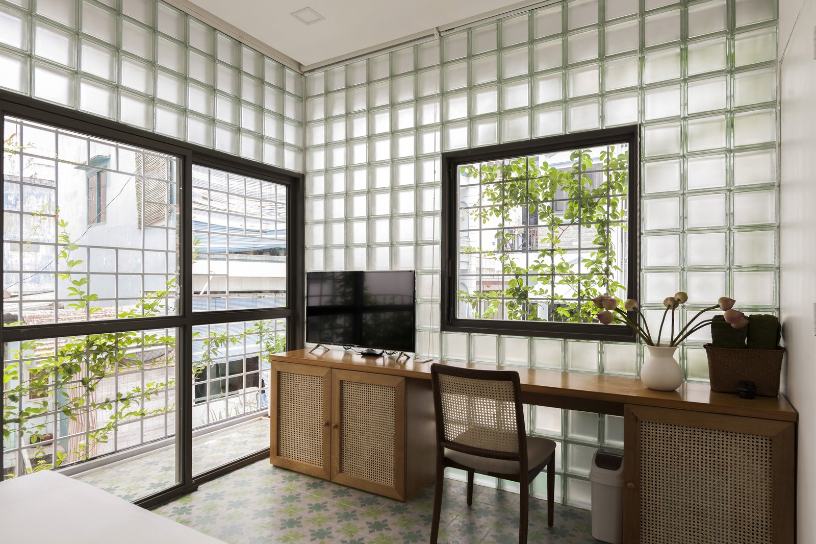 Bedroom, Recessed Lighting, Chair, Ceramic Tile Floor, and Porcelain Tile Floor A sliding glass door opens the master suite to the balcony and the city landscape beyond.  Photo 9 of 12 in This Vietnamese Micro Home Is as Practical as It Is Radiant
