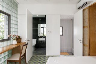Handmade deep green ceramic tile covers the wall in the master bath.