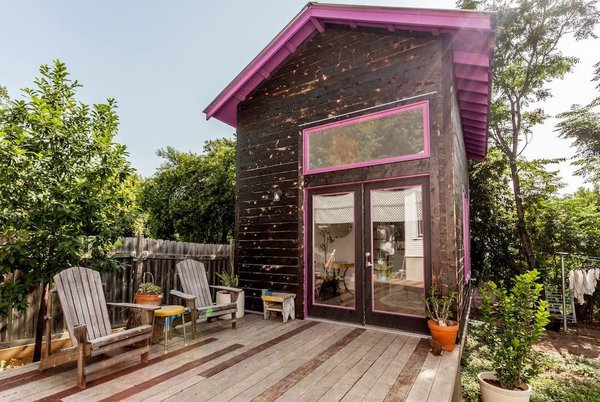 The wood-clad tiny home is marked by its pink-painted soffit and window and door frames.