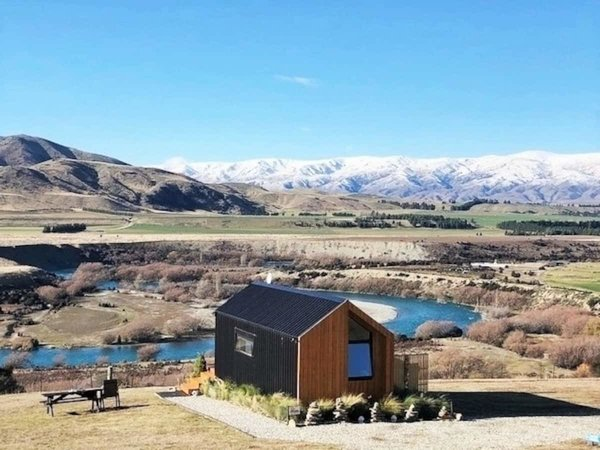 The Otago, New Zealnd, tiny home accommodates two people and is employed with large windows that flood the home with sunlight and views of the epic landscape.