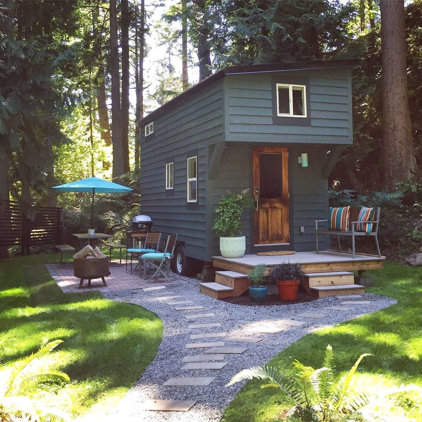 This island tiny home is sided with dark green-painted wood that blends into its wooded natural surround.  Photo 8 of 24 in Check Out These 23 Tiny Houses Perfect for an Autumn Getaway