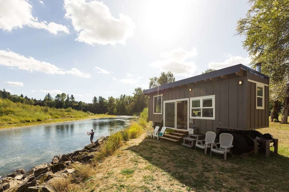A converted military ammunition trailer, the Tiny River House was crafted using reclaimed wood and industrial accents.  Photo 21 of 24 in Check Out These 23 Tiny Houses Perfect for an Autumn Getaway