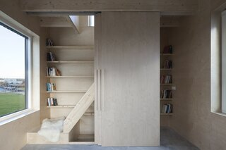 A built-in pine bookcase integrates with the staircase and climbs one of the walls on the first and second levels.