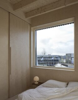 The bedroom, which is located on the third level, is finished with birch panels on the walls.