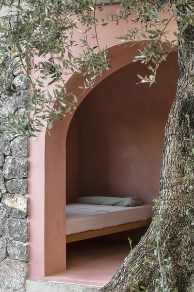 The bedroom area in the pink house is framed by an arch opening.