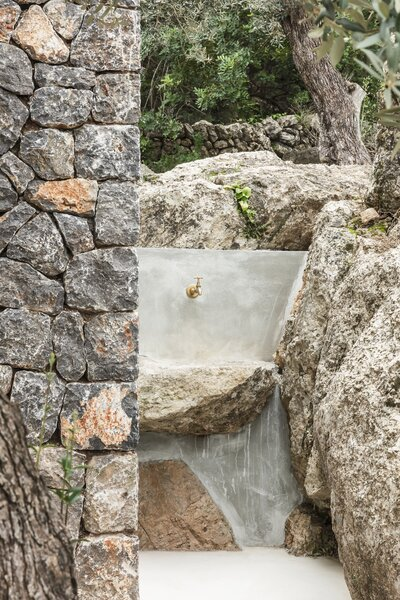 An outdoor shower built into the stone is located at the rear of the tiny house.