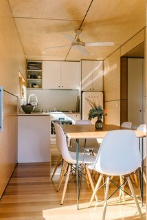 The home's entry opens to the kitchen and dining area in the first shipping container. Ecoply plywood walls, ceilings, and cabinetry, along with Tasmanian oak flooring, add a warm contrast to the exterior metal cladding.