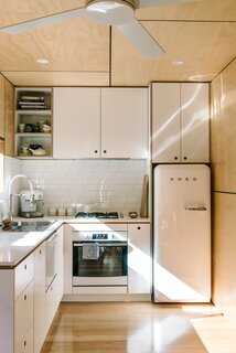 Low-VOC, zero-formaldehyde white plywood cabinets, a subway-tile backsplash, and stone counters run through the kitchen.