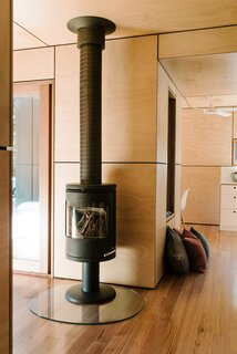 The living area, housed in the second container volume, features a vintage metal stove.
