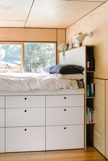 The built-in bed features a clever dresser system and a headboard that doubles as a bookshelf.