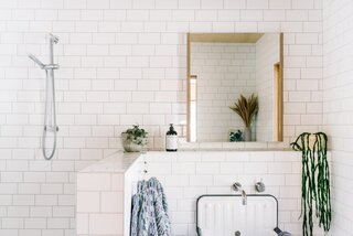 Partial walls and white subway tile create a spacious feeling for the bathroom.