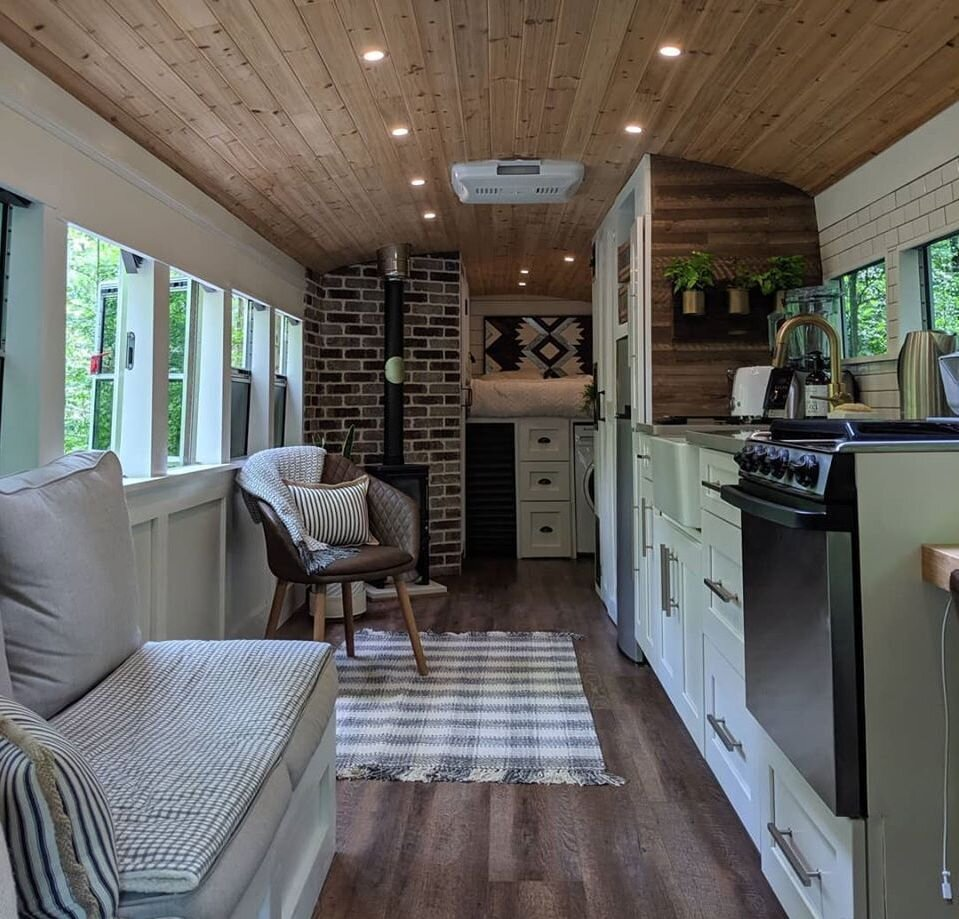 Living Room, Sofa, Medium Hardwood Floor, Ceiling Lighting, Chair, and Corner Fireplace You can follow Robbie and Priscilla's converted school bus on Instagram at @going_boundless.  Photo 12 of 12 in 12 Inspiring Tiny Homes That Were Entirely DIY'ed