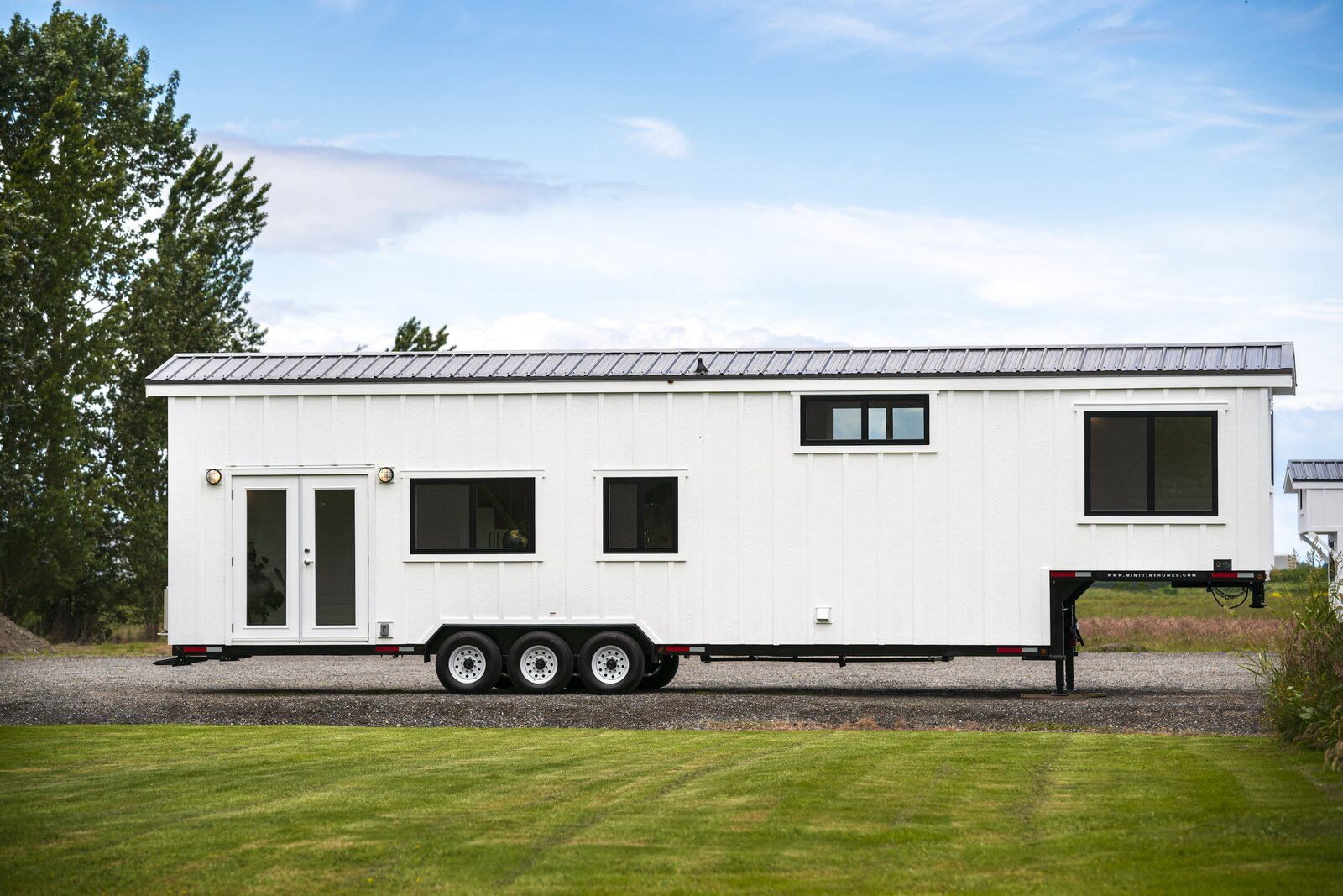 """Exterior, Tiny Home Building Type, Metal Roof Material, Gable RoofLine, and Wood Siding Material Traveler's Paradise, Megan Moore's 416-square-foot tiny home designed and built by Mint Tiny Home Company, is clad with white board-and-batten siding and a standing-seam metal roof. The founders of Mint Tiny Home Company, Brian and Shannon Perse, established the business in 2014 as a reaction to rising housing prices in British Columbia. """"They quickly realized the problem was not just local, but rather a crisis going on all across the U.S. and Canada,"""" says marketing and social media coordinator Jordan Bates. """"They work with each client and build a dream home that works for their specific lifestyle, budget, and values.""""  Photo 2 of 11 in One Family's 416-Square-Foot Digs Expand the Limits of Tiny Home Living"""