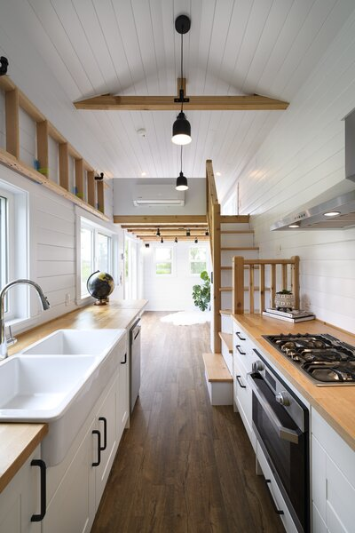 The interior of the tiny home, which features a sleeping loft above the living room, is finished with vinyl flooring and white pine walls.