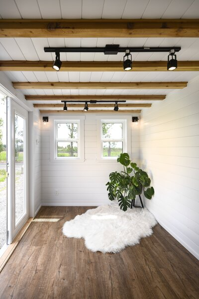 Sunlight pours into the living area, which connects to the natural landscape via glass doors. Exposed cedar beams provide texture and warmth for the space.