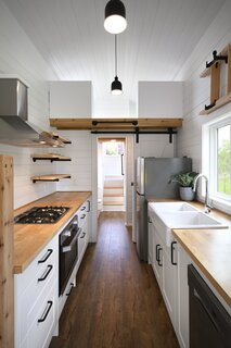 A sizable primary bedroom and a sleeping loft above a bathroom flank the kitchen area.