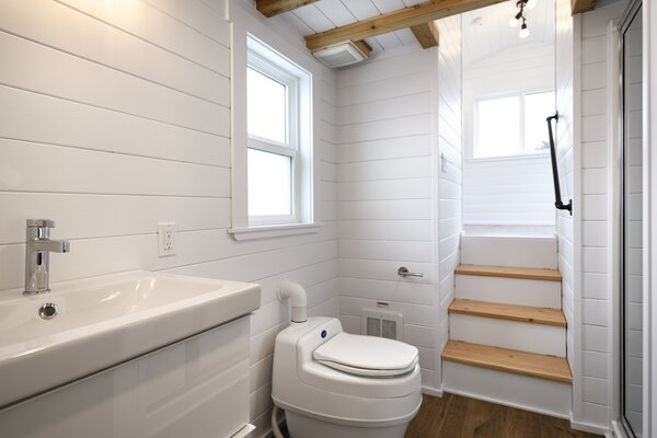 The bathroom is outfitted with a composting toilet and a large window. The designers placed storage beneath the stair treads that lead to the main bedroom.