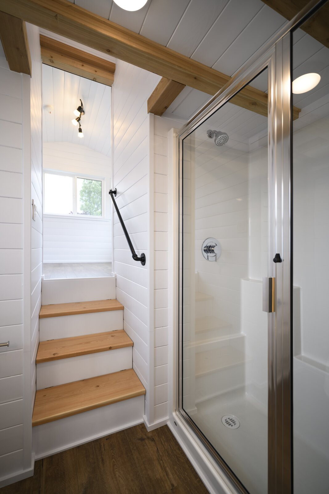 Bath Room, Vinyl Floor, Ceiling Lighting, and Enclosed Shower The bathroom features a shower with a glass door and a partial glass wall.  Photo 7 of 11 in One Family's 416-Square-Foot Digs Expand the Limits of Tiny Home Living
