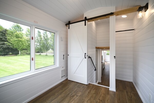 A sliding barn door closes off the main bedroom from the rest of the tiny home.