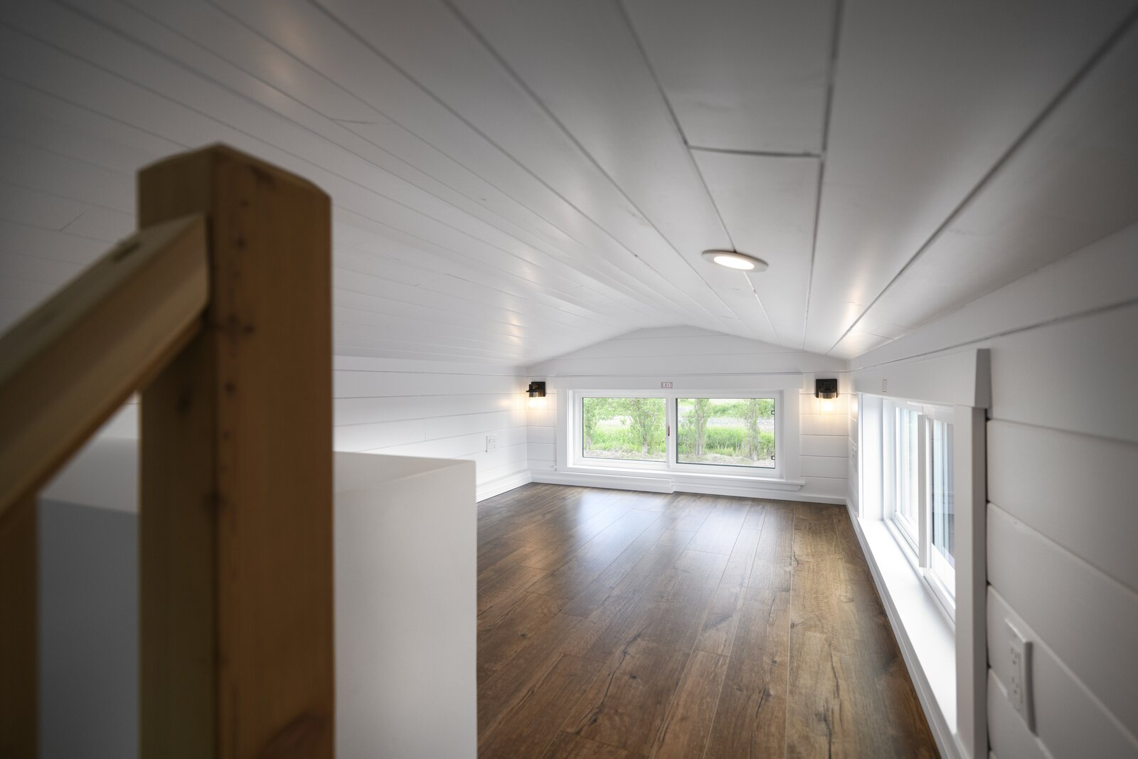 Bedroom, Ceiling Lighting, and Vinyl Floor The sleeping lofts are flooded with natural sunlight thanks to multiple windows.  Photo 10 of 11 in One Family's 416-Square-Foot Digs Expand the Limits of Tiny Home Living