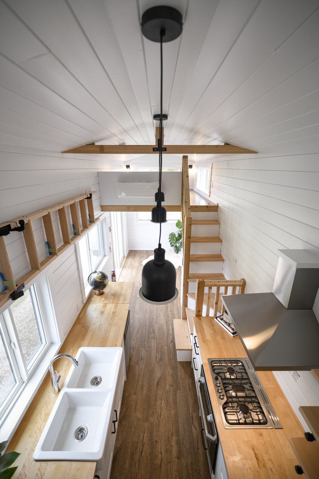 Kitchen, Laminate, White, Ceiling, Range Hood, Wood, Vinyl, Drop In, and Cooktops Ceilings that are over 10 feet tall provide a feeling of airiness for the tiny home.  Kitchen Vinyl White Range Hood Photos from One Family's 416-Square-Foot Digs Expand the Limits of Tiny Home Living