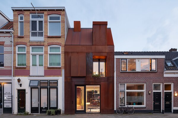 The Cor-Ten steel of the front facade wraps around the roof, the chimney, and a dormer, lending a sculptural aesthetic.
