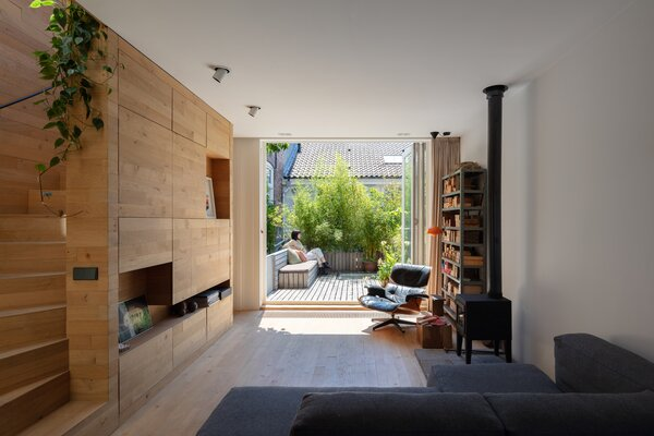 On the second level, the design team arranged a living area that opens to a balcony and deck area. The built-in wall storage is crafted from oak.