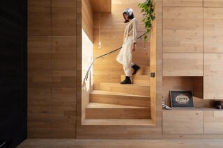 The oak staircase pivots as it leads from the bedroom on the top level to the living room on the second level.