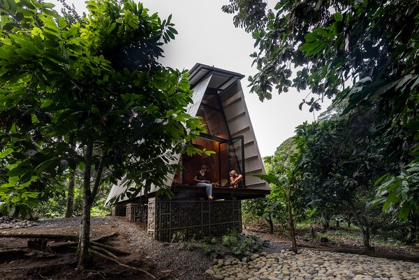 The cabin is elevated by a system of gabions that act as its foundation and prevent flooding. The rear facade features a teak decking that allows visitors to sit outdoors among the treetops.