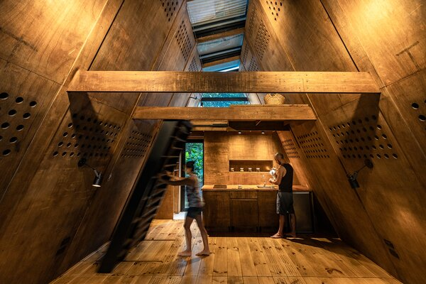 A large metal staircase near the kitchen folds up and provides access to the loft-like sleeping area.