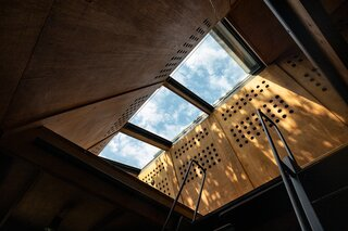 The outer layer of the roof slides open, revealing a glass ceiling that lets in sunlight and frames views of the sky.