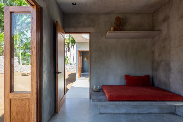 The living area, which is open to the kitchen and adjacent to the courtyard, features a built-in concrete daybed with a large red cushion.