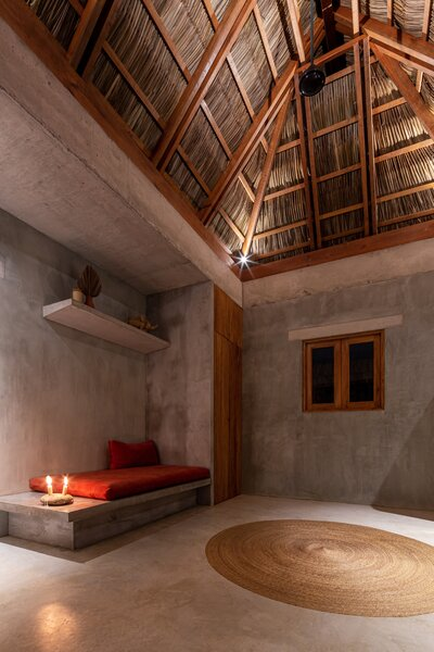 A tall, thatched ceiling of dried palm leaves in the combined kitchen and living area facilitates natural ventilation.