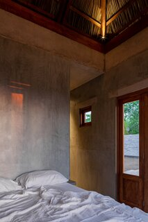 The larger stucco-clad volume houses the bedroom and the bathroom.