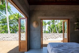 Folding doors made of wood and glass open the private volume to a view fringed with tall palms.