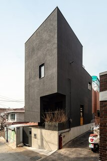 The exterior of the tall and narrow home is sided with black-painted stucco.