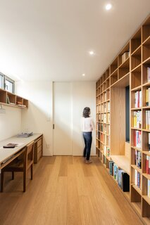 The office on the second level is outfitted with a built-in desk and bookcase that spans the length of the walls.