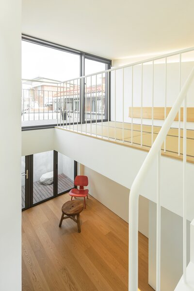 A loft-like sleeping area on the fourth level lies just above the living room, which is located on the third level. Glass doors open to terraces on both floors and flood the rooms with natural light.