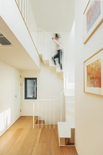 A white-painted steel-plate staircase leads from the third floor to the attic level.