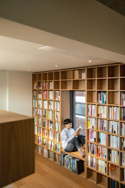 A wall on the second level features a built-in bookcase with a reading nook.