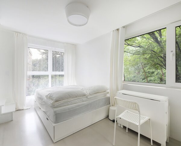 The third-level bedroom is also spare, drawing attention to the picturesque greenery outside.
