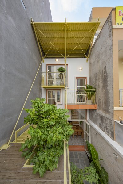 Double Roof House, a residence and small business designed by Khuon Studio, sits on a narrow lot that measures 44 by 183 feet in Ho Chi Minh City.
