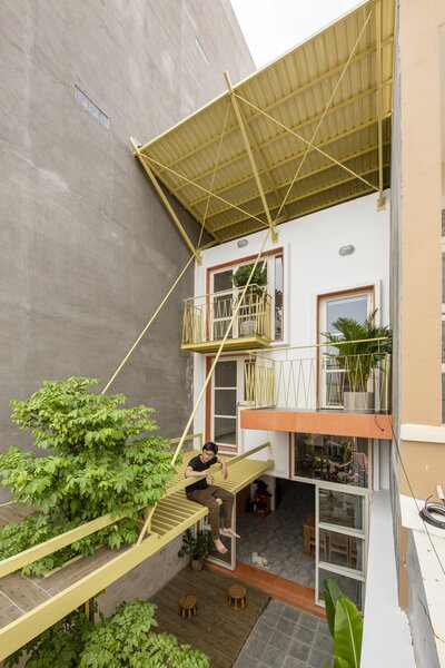 Three brightly colored balconies and an overhanging roof define the home's front facade.